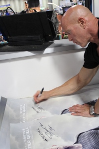 Bruno Gunn intensely signing posters